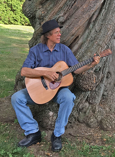 Larry playing guitar under a tree